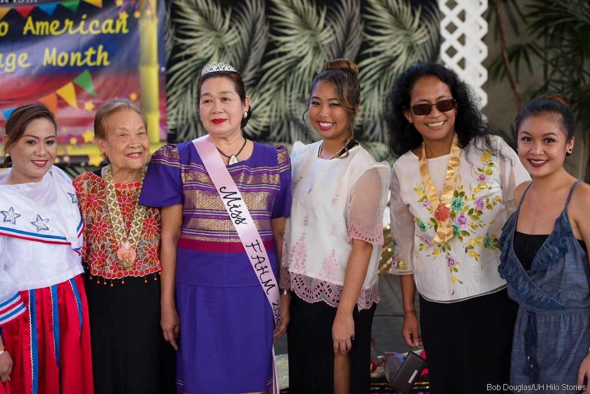 Group of women in traditional clothing. Queen of event with crown at center.