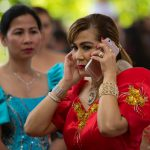 Woman in traditional attire on cell phone.