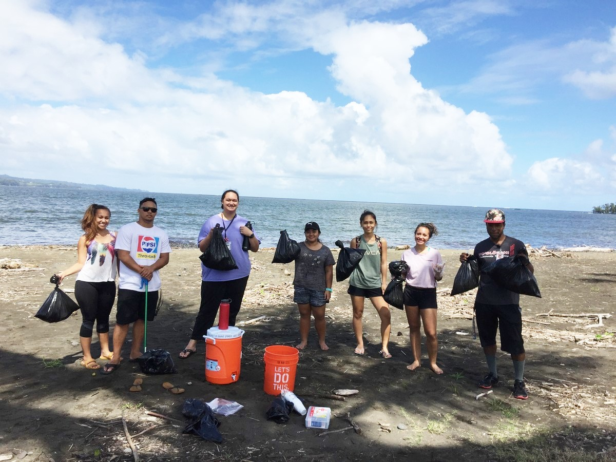 Group of students at Hilo Bay with garbage bags full of rubbish.
