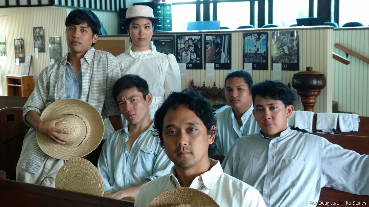 Six cast members in white period costumes, three hold straw hats.