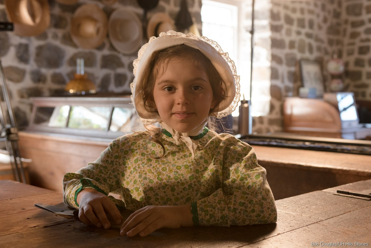 Younf girl in period costume with bonnet.