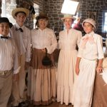Group in store, period costumes, soft whites and browns.