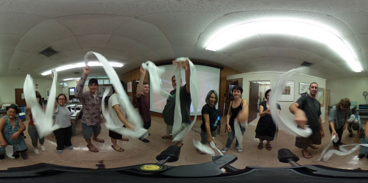 The whole class getting a 360 photography tutorial, each student is moving paper through air.