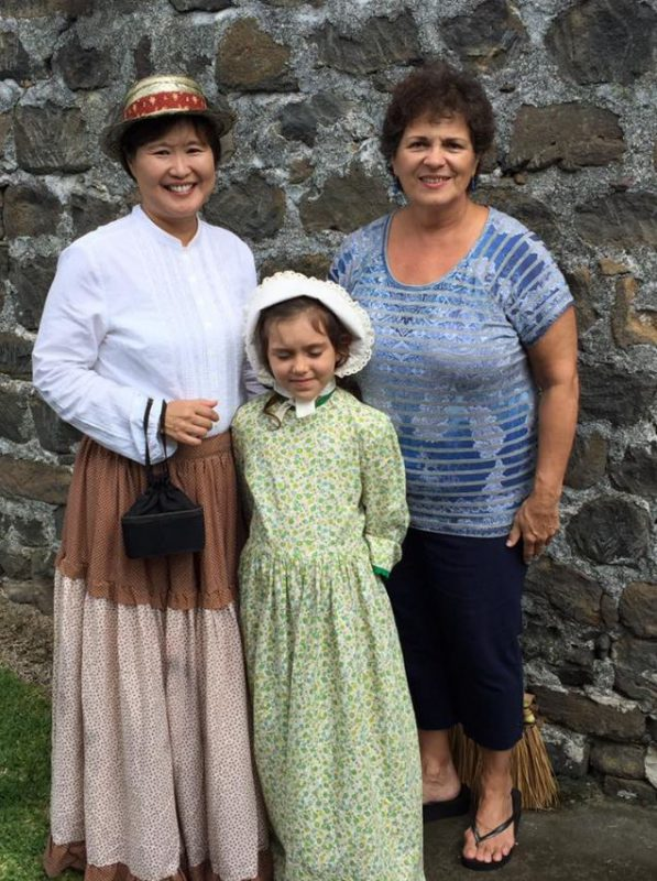 Patsy and Jackie with young girl. Stone wall background.
