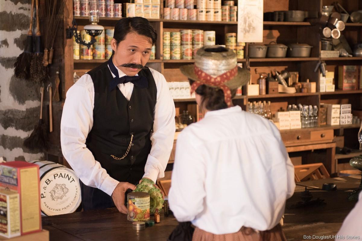 Kimo Apaka in the role of Honoka'a businessman Katsu Goto, speaks to woman at counter of store.