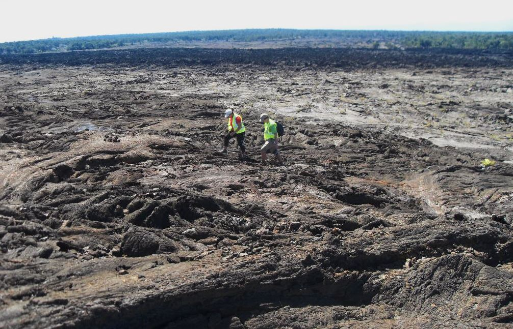 Two people walking over a vast lava flow.