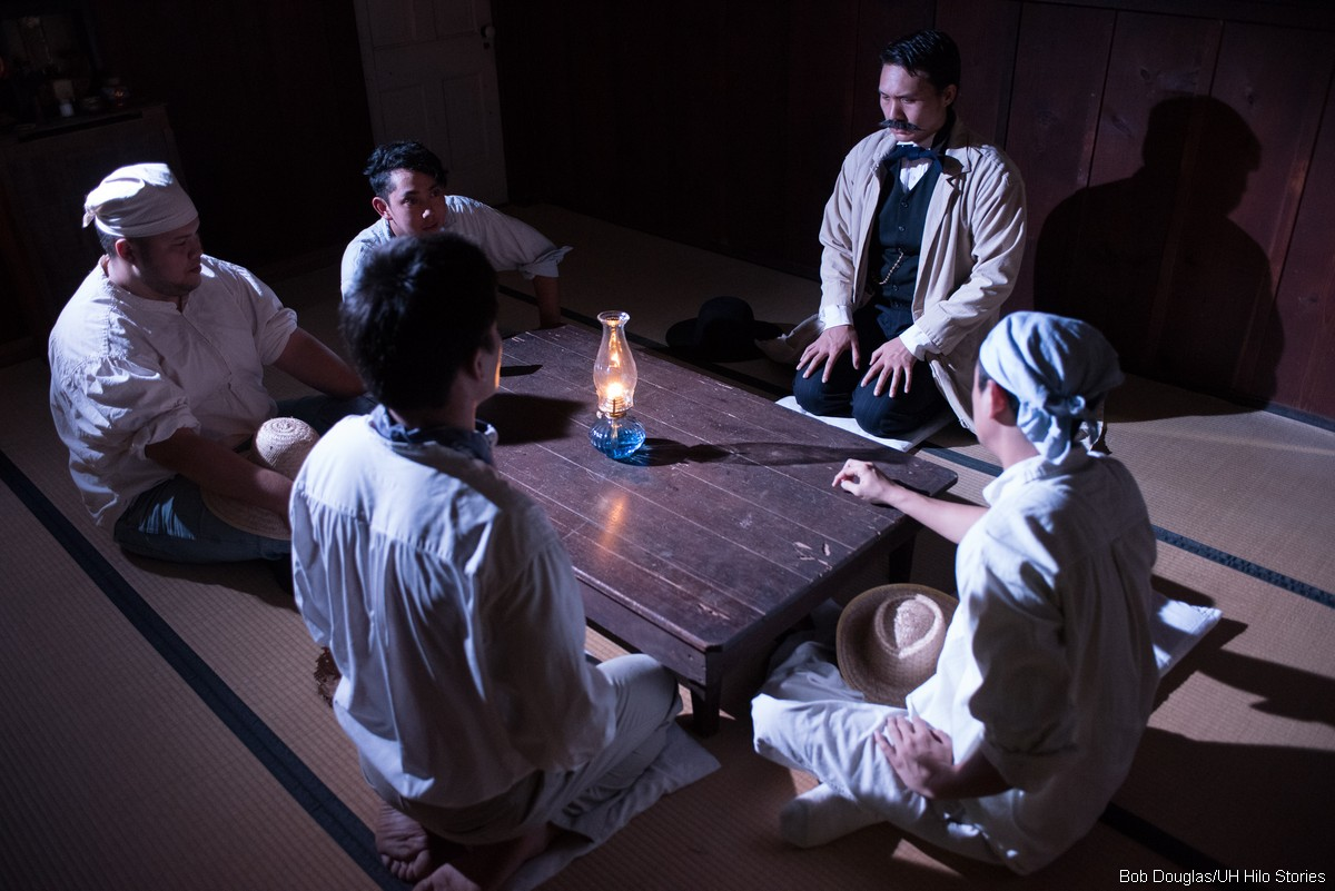 Group of men meeting around a low table. Kerosene amp on center of table.