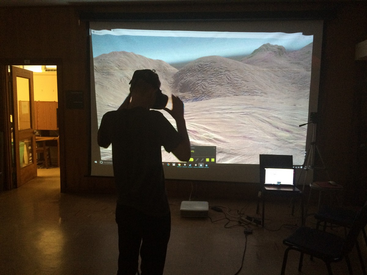 Students with headset working on large screen.