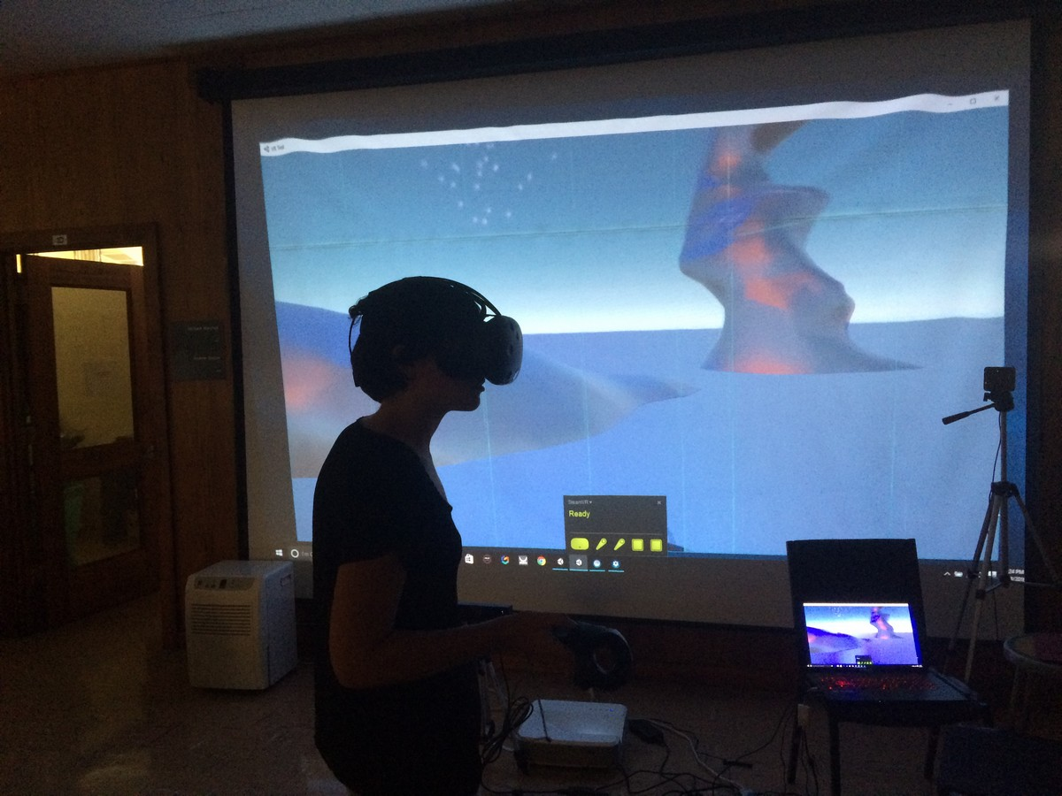 Student in virtual head set watches scans on screen.