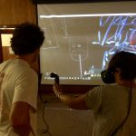 Students working on big screen.