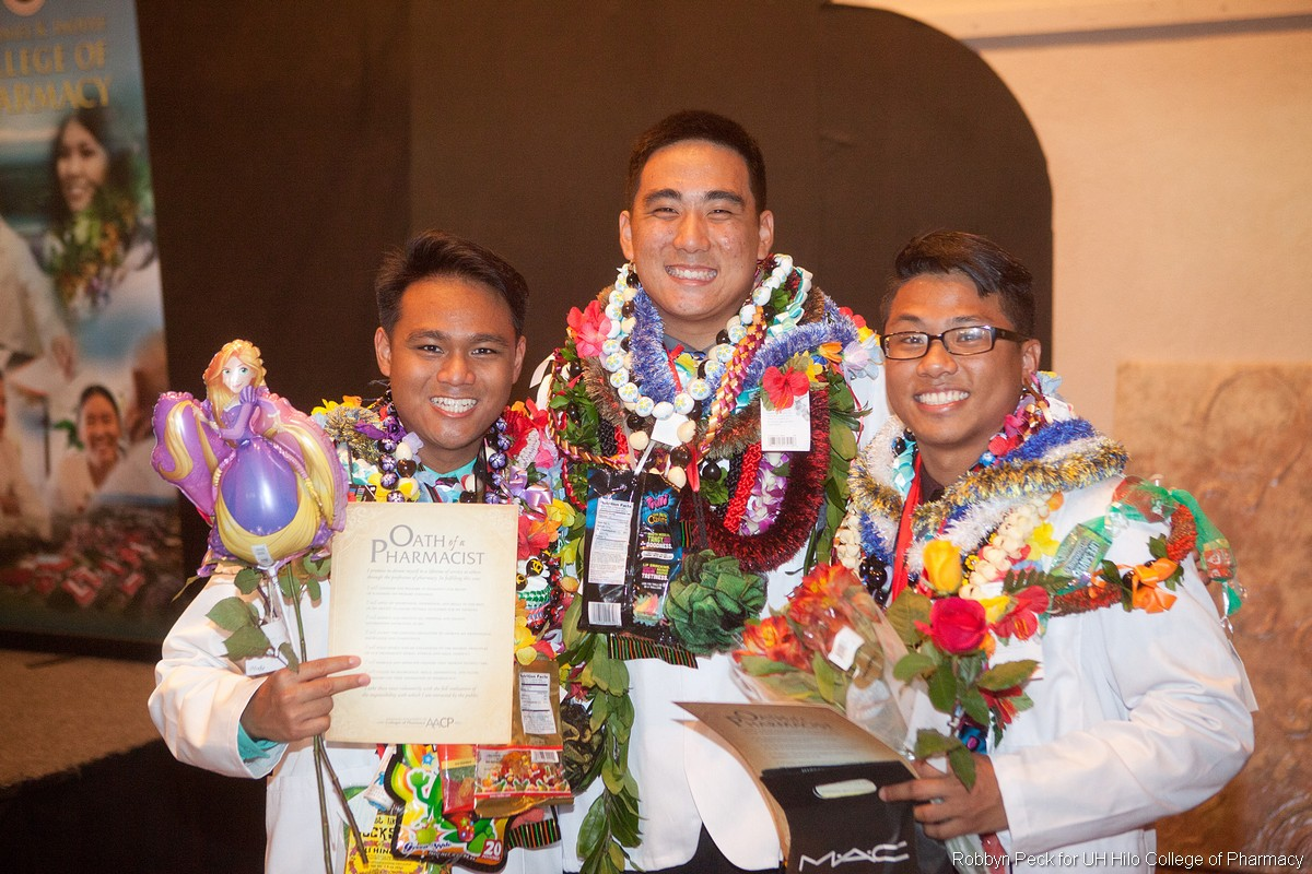 Three students in white coats, lei.