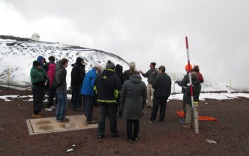 Maunakea ranger briefs group of visitors on safety. Snow in background.