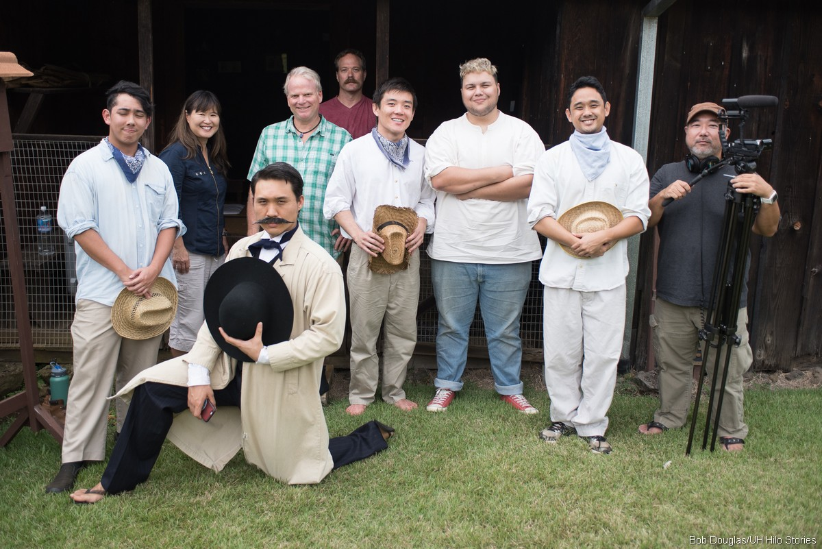 A few cast and crew pose for photo. Cameraman at right. Cast is in costume.