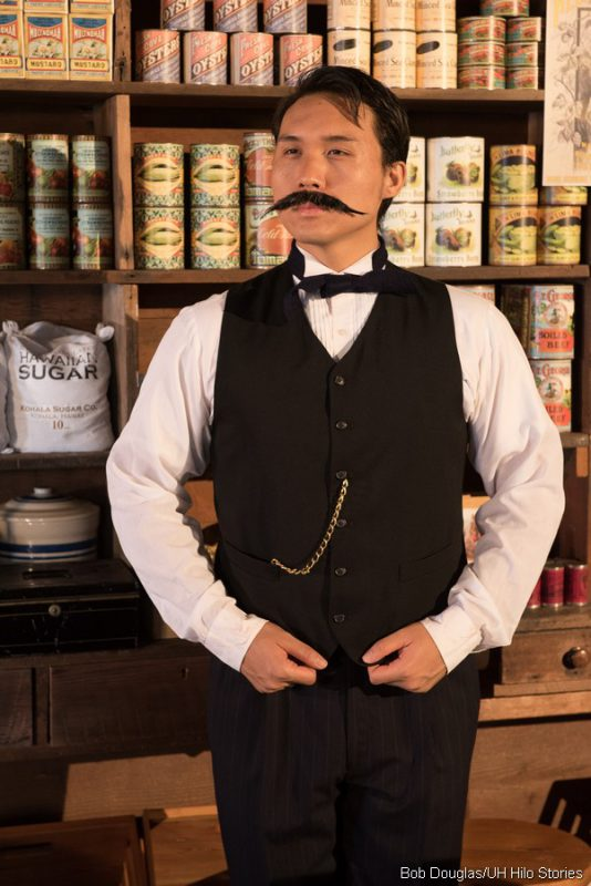 Kimo Apaka as Katsu Goto, in white shirt, black pants and vest, 19th century style clothing. He has a wide, long mustache.