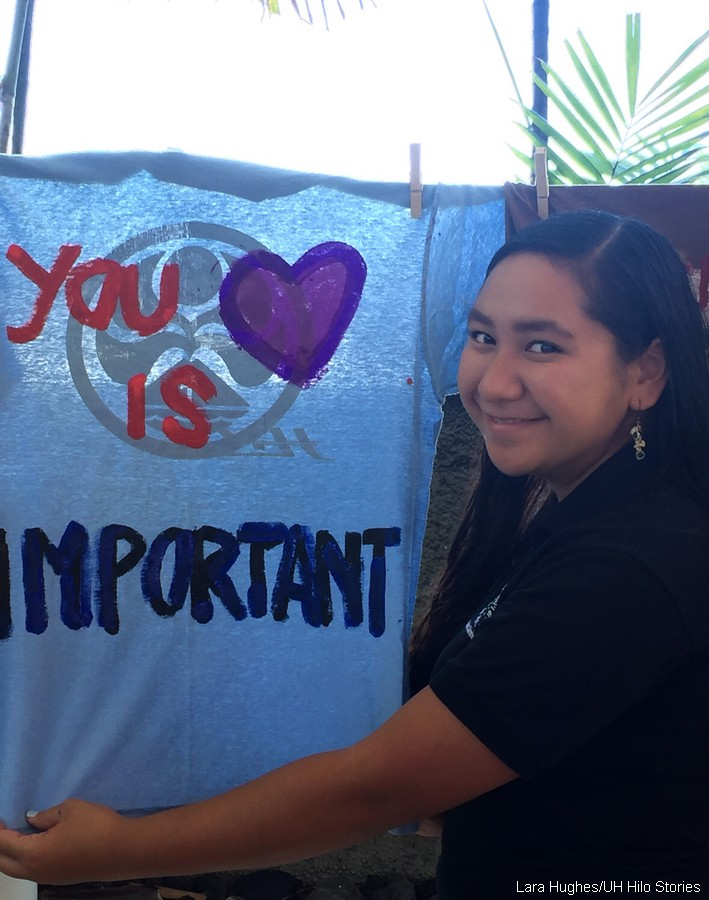 "Juvette Kahawai stands next to a t-shirt with the words ""You is IMPORTANT."""