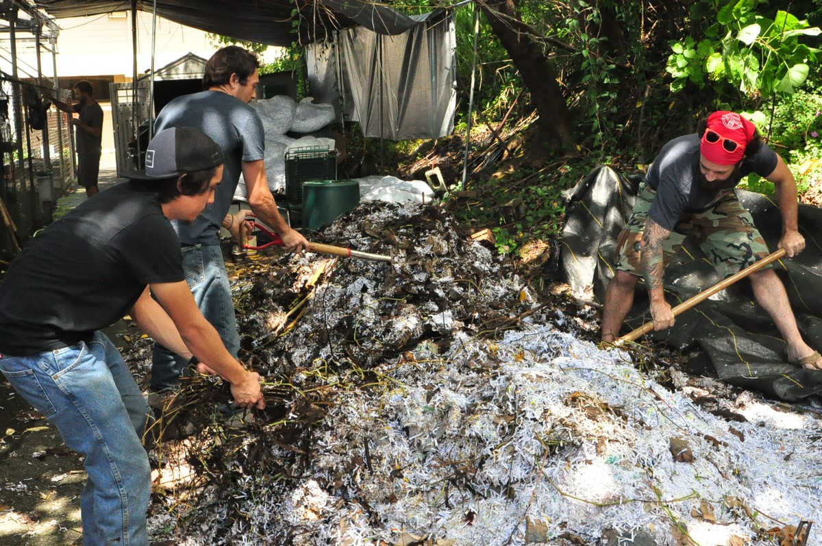 Four men working with tools to turn a large compost pile.