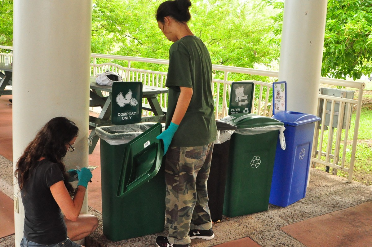Two students collect recycled materials from green and blue bins on the campus plaza.