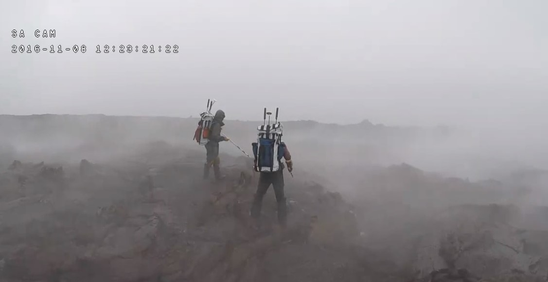 Simulation astronauts on rocky landscape with backpacks and mist all around.
