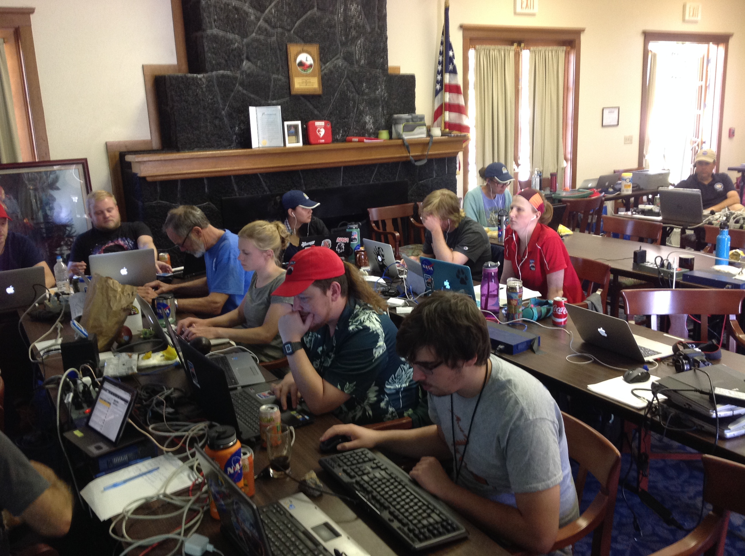 Students at tables seriously working on computers and laptops.