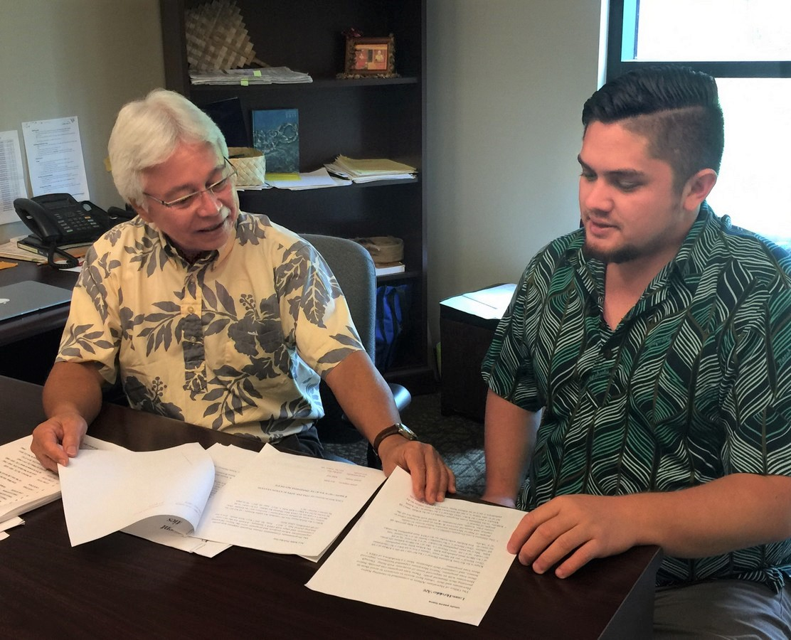 Larry Kimura sits with student Kamalani Johnson, they are looking at papers on the desk in front of them.