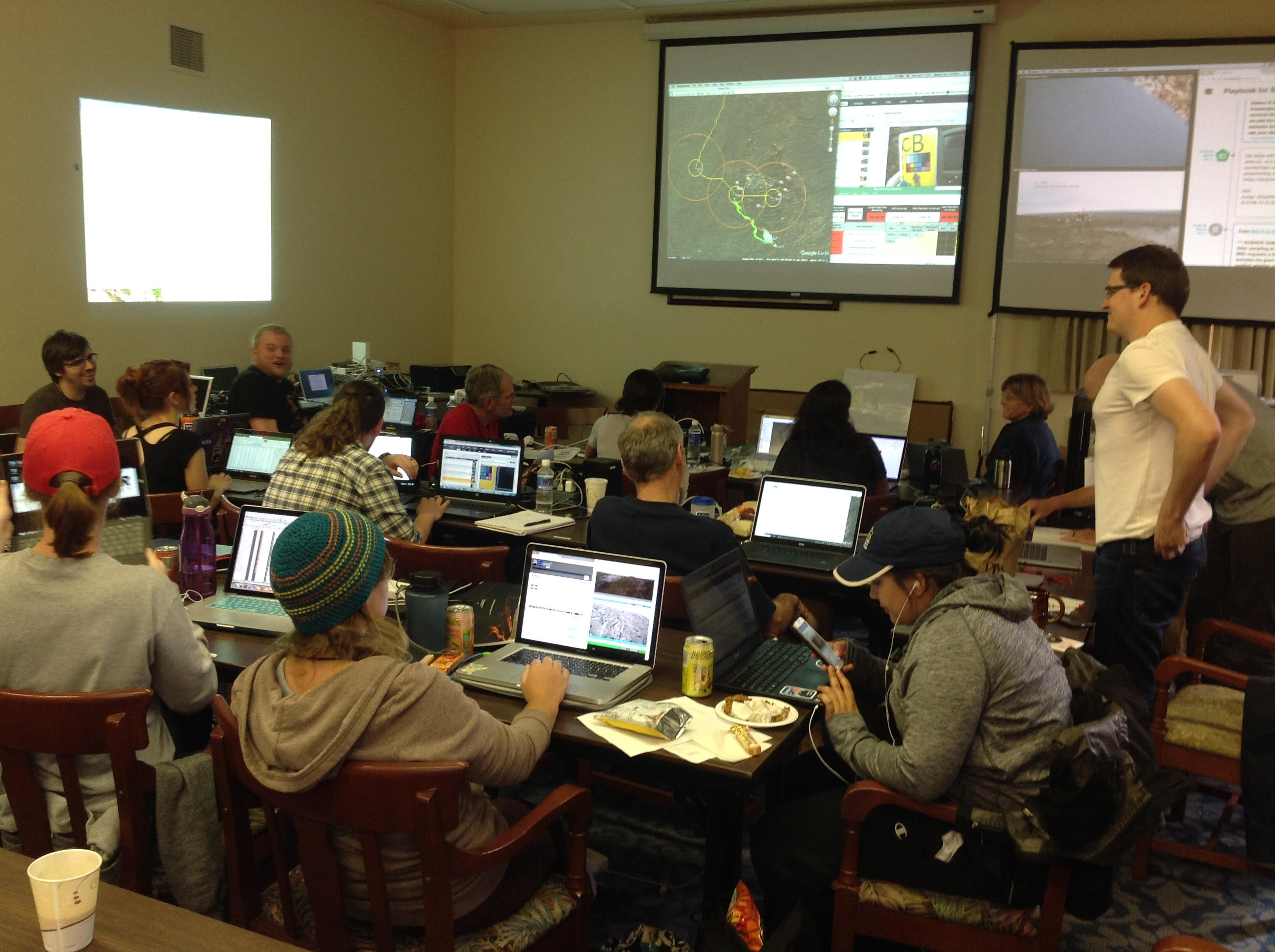 About a dozen people at desks working on laptops, a mapping image is on an overhead screen at the front of the room.