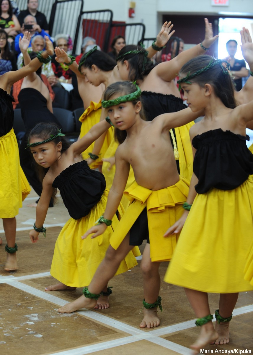 Keiki dancing, right toes pointed out, one arm up, the other down. They are in black and yellow.