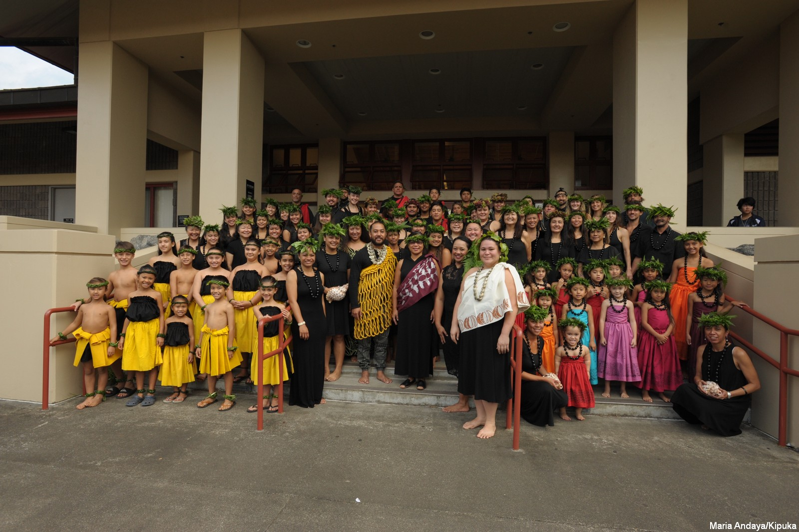 Large group of keiki and kumu on steps for group photo. Keiki are in colorful dress, adults are in black.