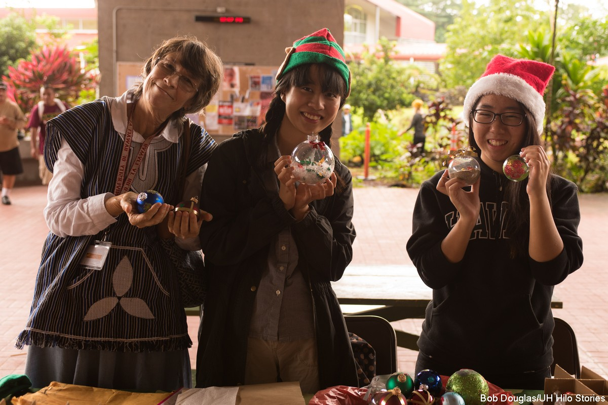 Students and advisor hold up ornaments. The two students have on Christmas hats.
