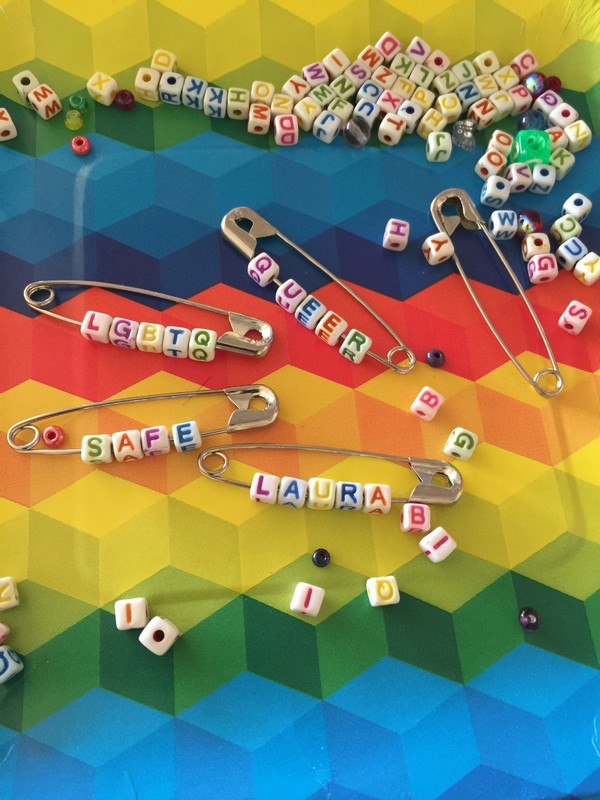 "Safety pins with tiny block letter beads threaded on  and spelling out ""safe"" and ""queer"" and ""LGBTQ."""
