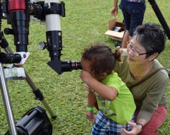 Stephanie Nagata and keiki exploring with telescope.