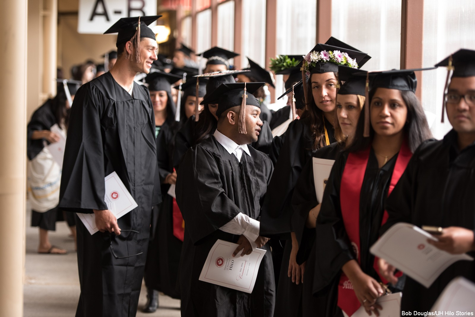 Candidates in cap and gown wait in line to enter venue.