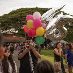Family entering venue, bringing balloons.