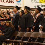 Candidates begin to stand row by row to come forward to receive diploma.