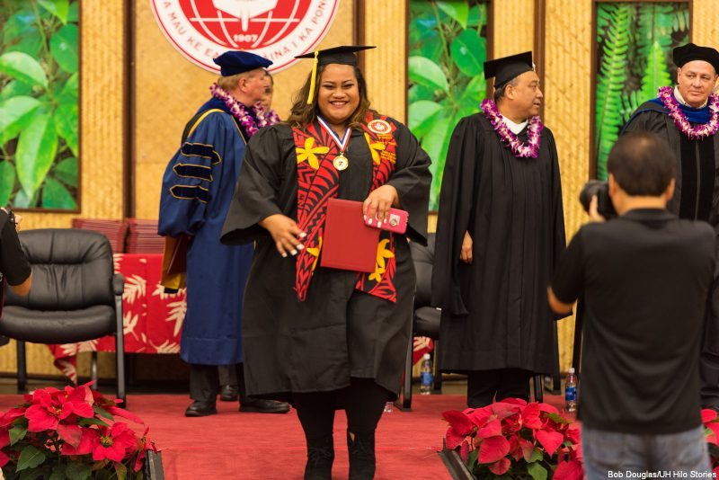 Female candidate walking down from dais holding diploma.
