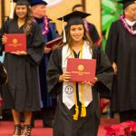 Candidate leaves dais with diploma.