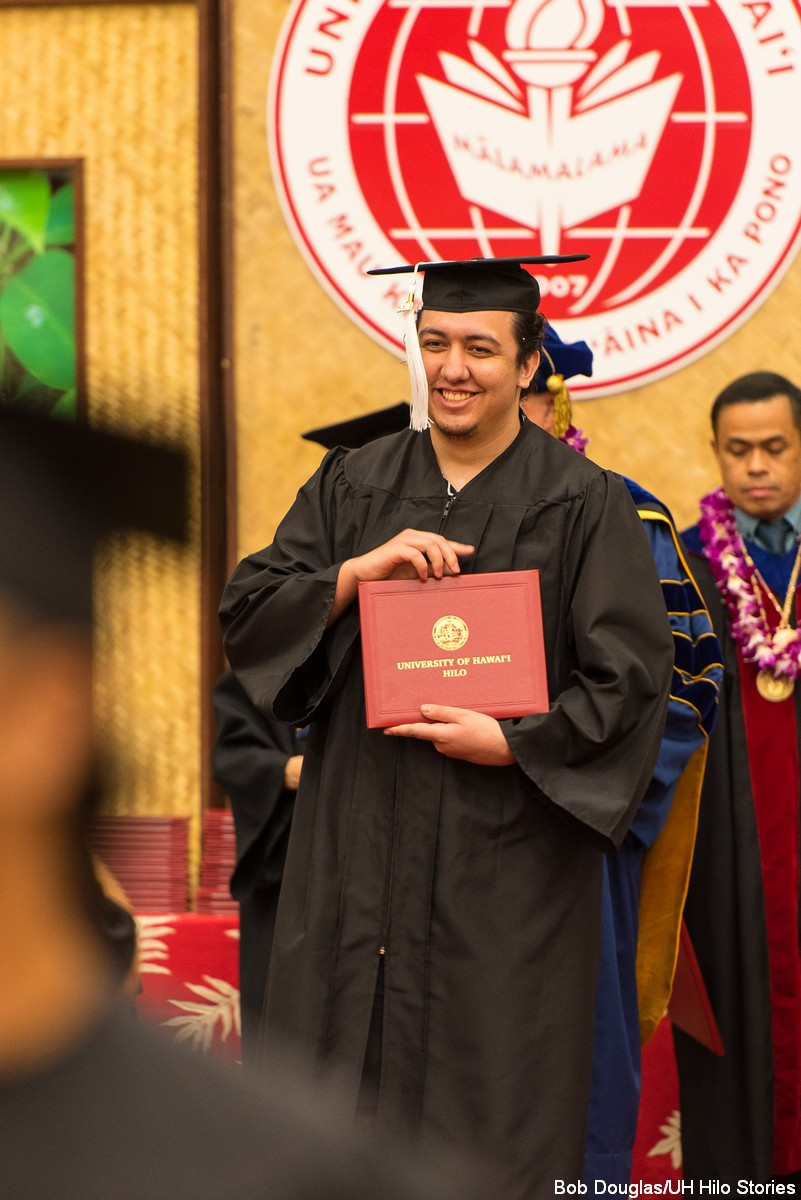 Male candidate walking down from dais holding diploma.