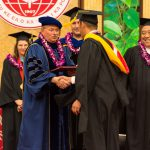 Chancellor shakes graduate student's hand after his hooding.