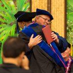 Chancellor embraces doctoral student.