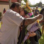 Graduate receives a congratulatory kiss.