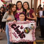 Graduate with family who brought a sign of celebration.