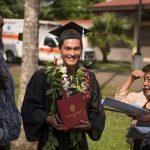 Graduate holds diploma.