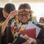 Graduate adjust her head lei.