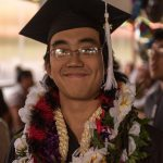 Smiling graduate with lei.