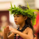 One keiki dancer, fern head lei and kukui lei.