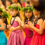 Group of young girls dancing in colorful dresses.