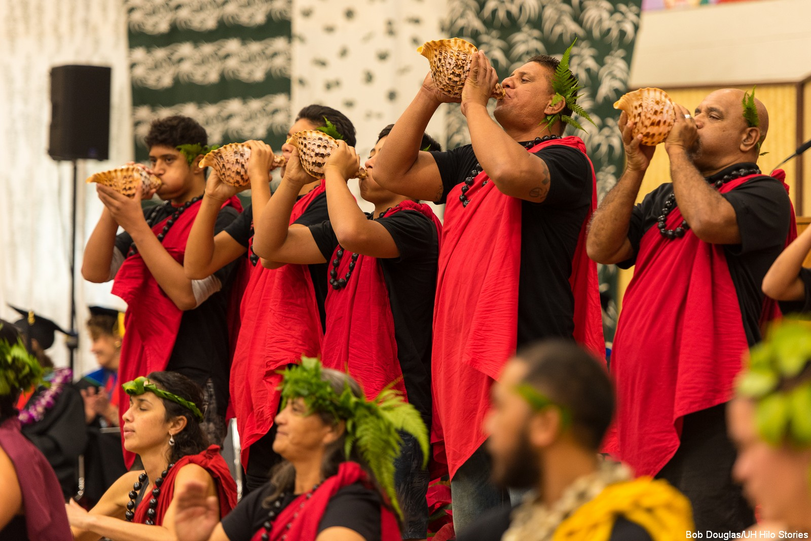 Group blows conch shells. Dressed in dramatic red and black.