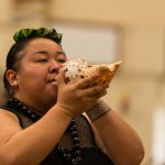 Woman blowing conch.