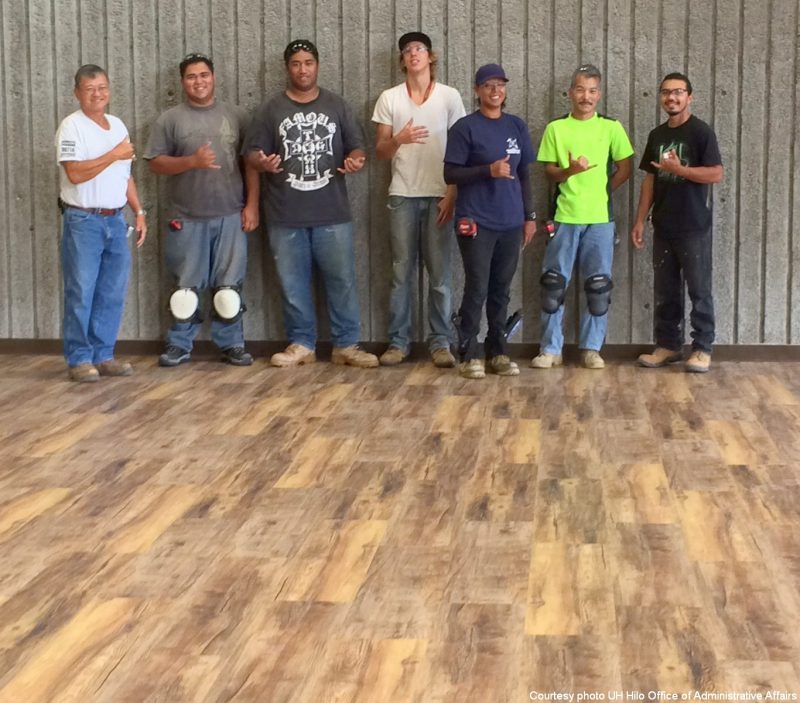 Workers gather for group photo, standing on new floor.
