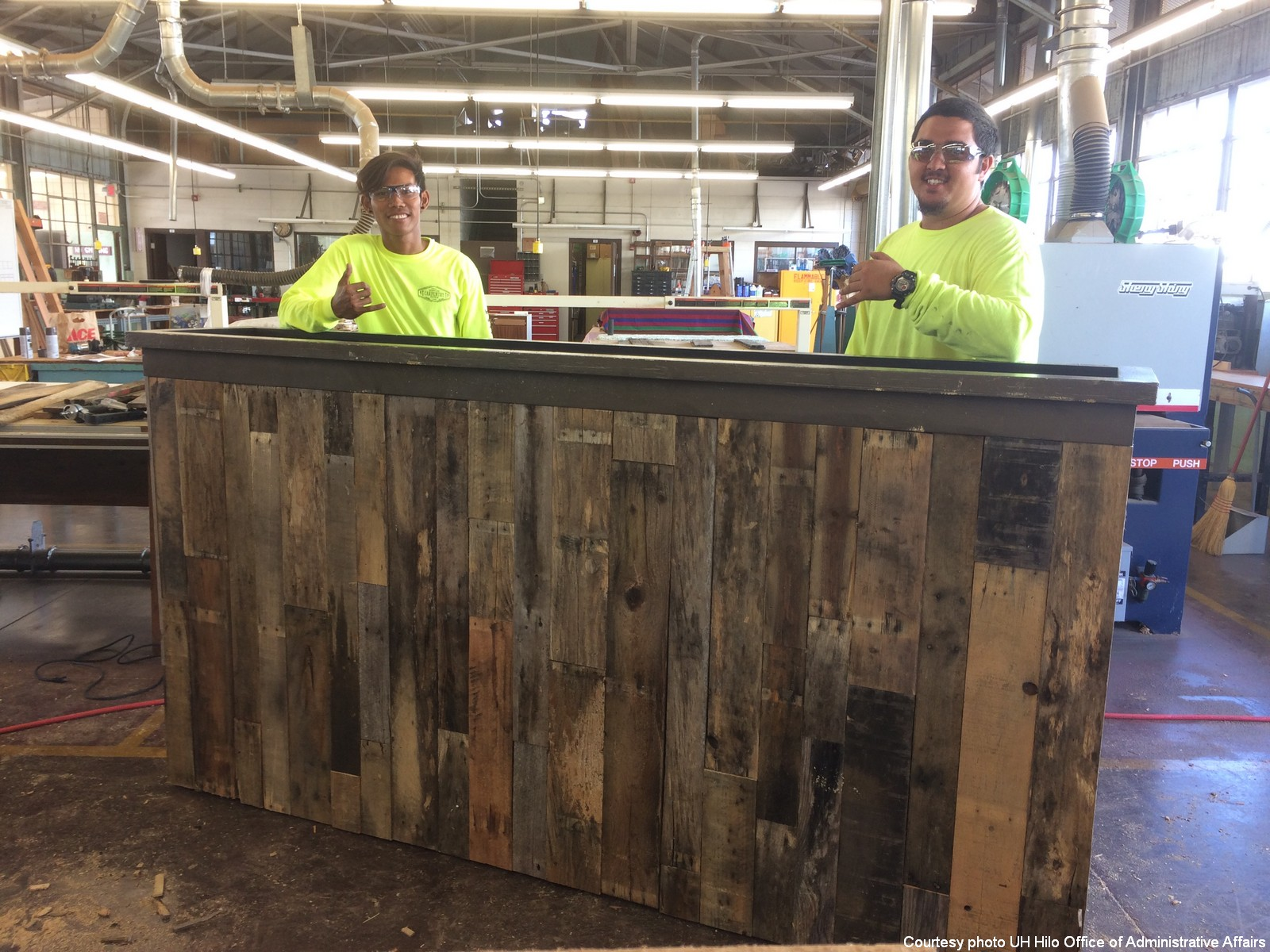 Two carpenters who refinished planters flash the shaka.