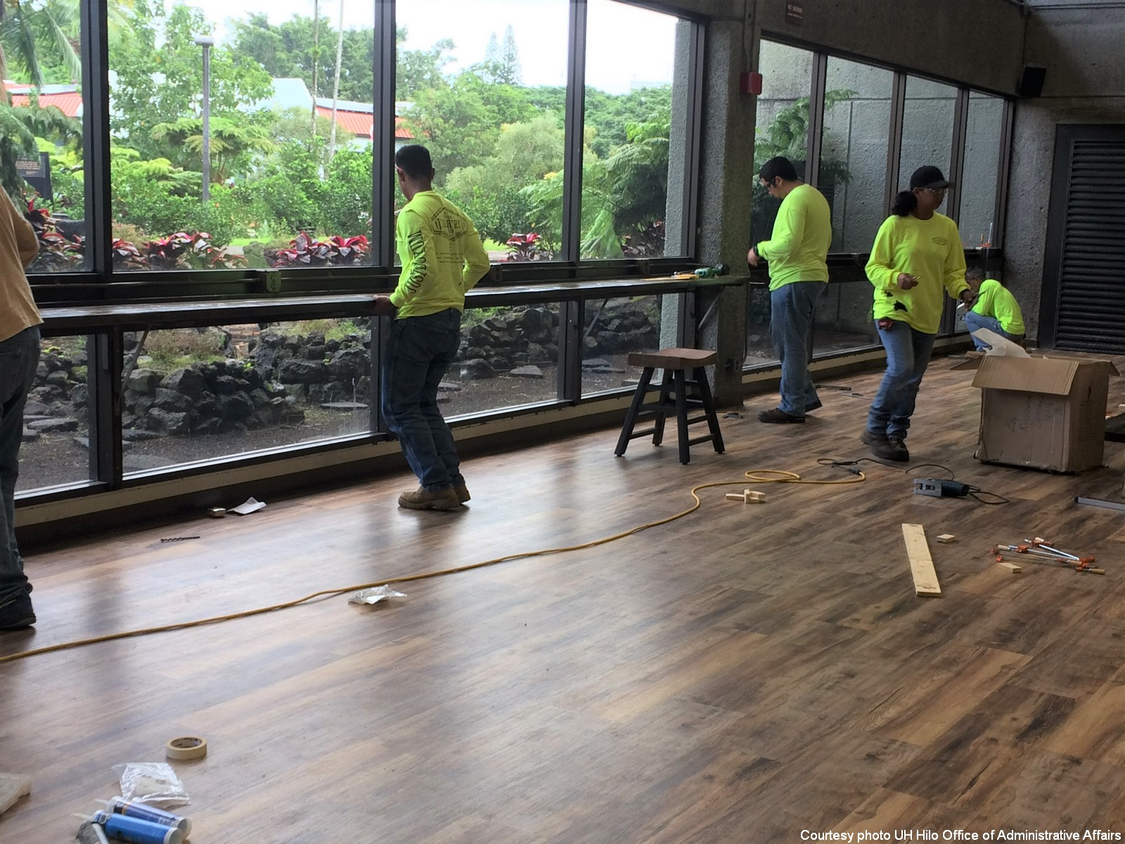 Workers install new counter in front of the windows looking out at gardens.